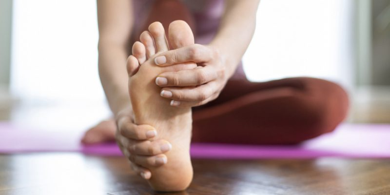 Woman practicing yoga for sore feet