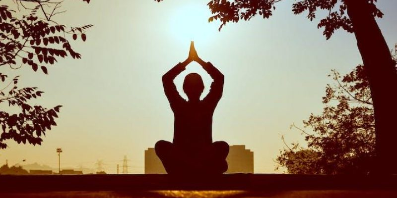 person sitting with legs crossed arms up in front of sunset for yoga and mental health