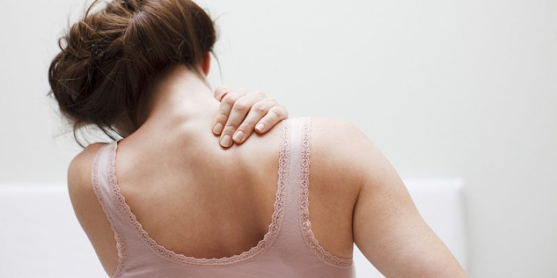 Woman massaging shoulder in need of yoga for tight shoulders