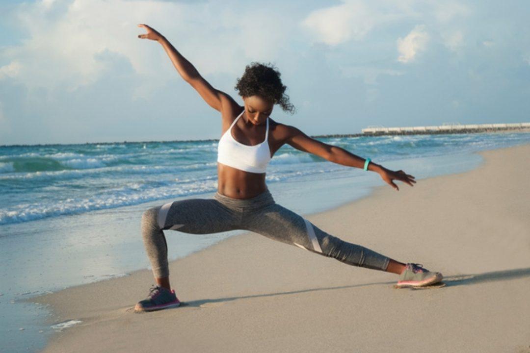 black woman doing yoga on beach
