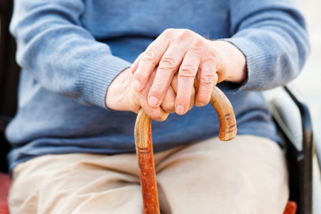 Elderly persons hands on cane
