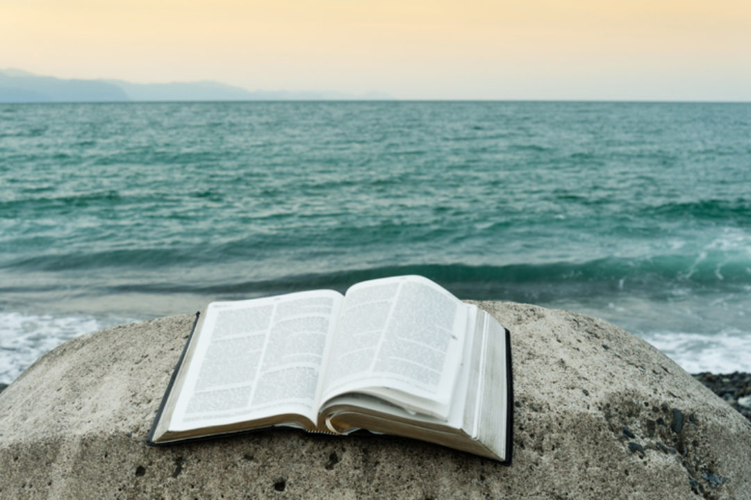 Open Bible on top of a rock in front of the sea of greenish waters and an orange sky.