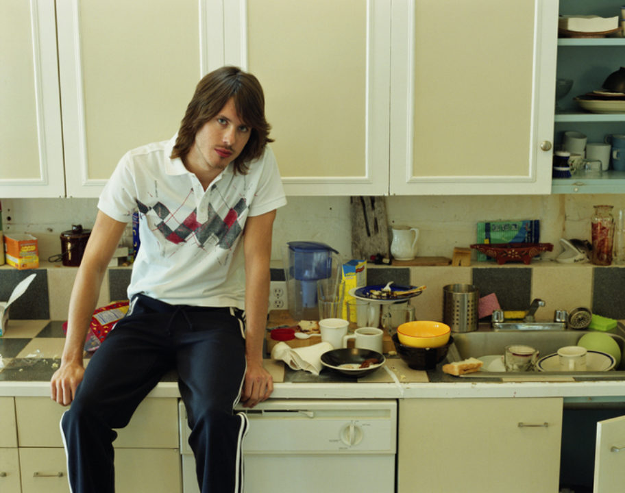Young man sitting on counter in untidy kitchen