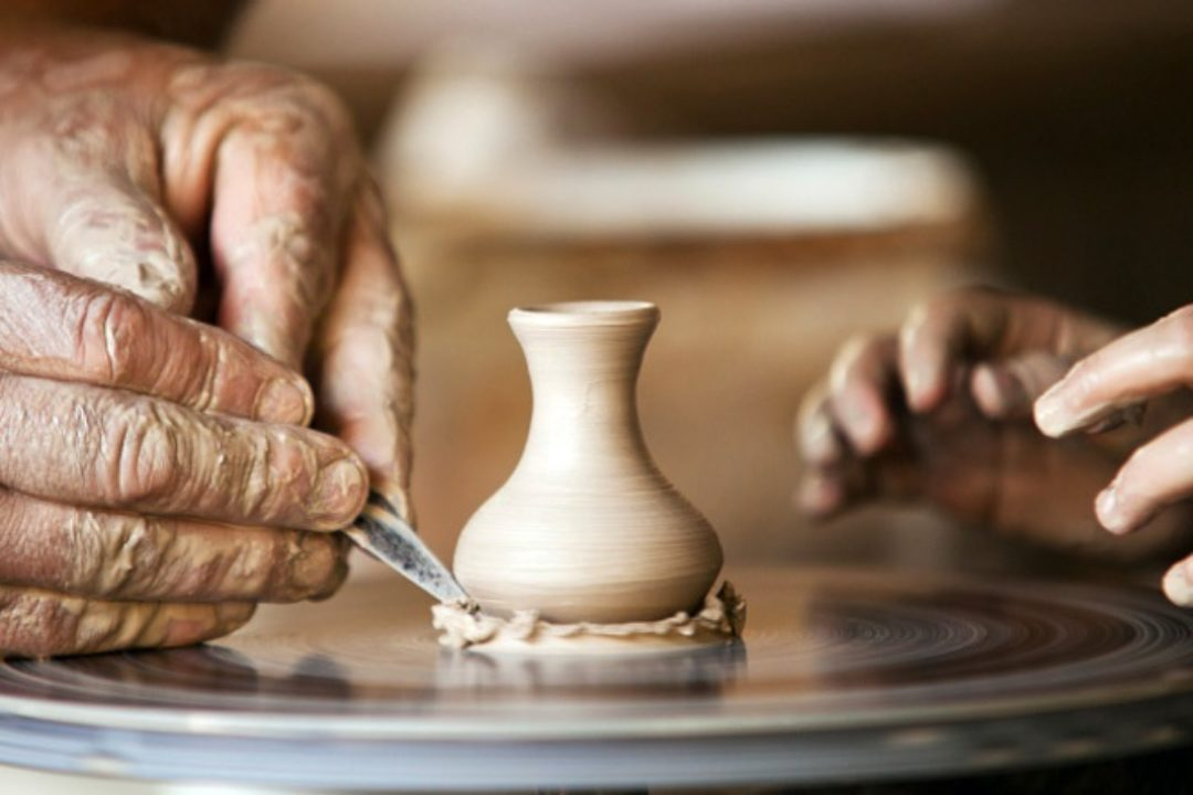 Two hands working on clay wheel