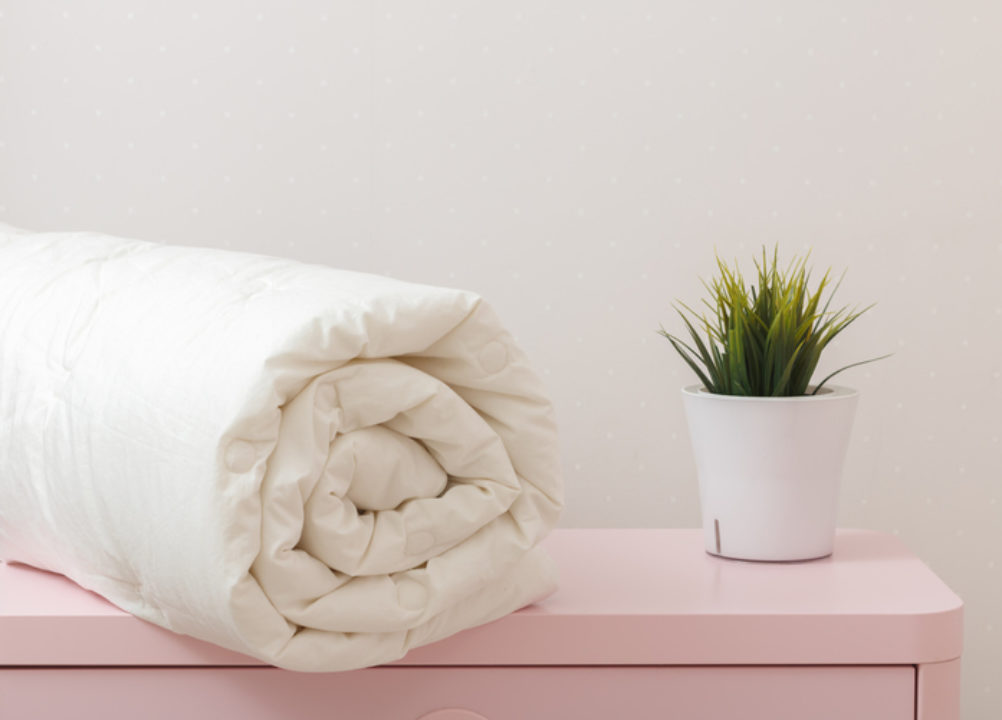 feather duvet, rolled up on table
