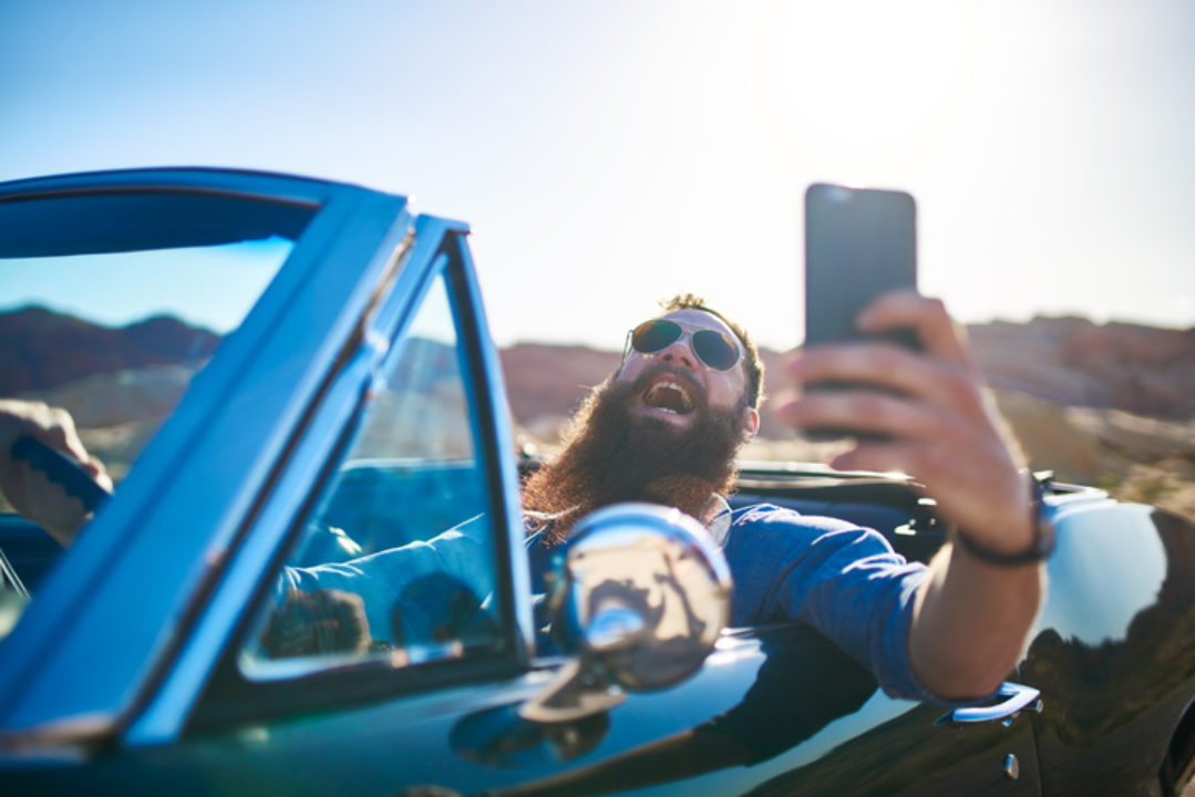 bearded man taking selfie while driving car