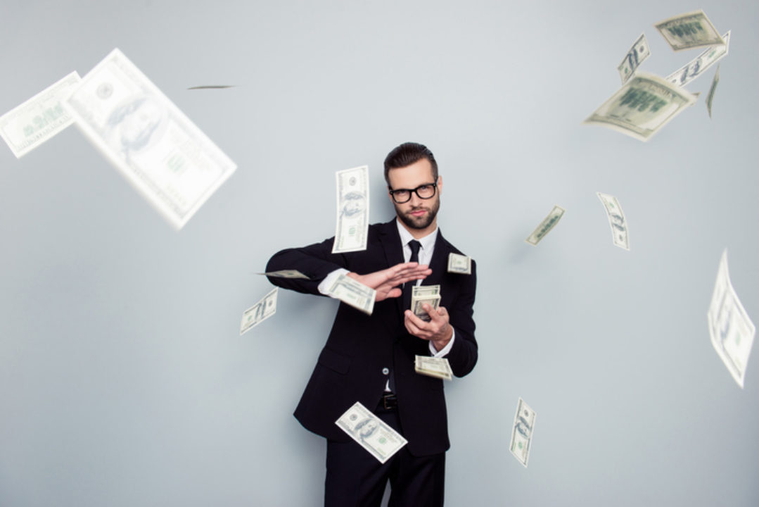 Man wasting money by throwing it