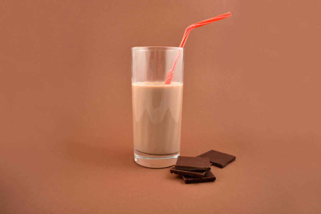 Chocolate milk with chocolate pieces. Glass of chocolate milk on a brown background.