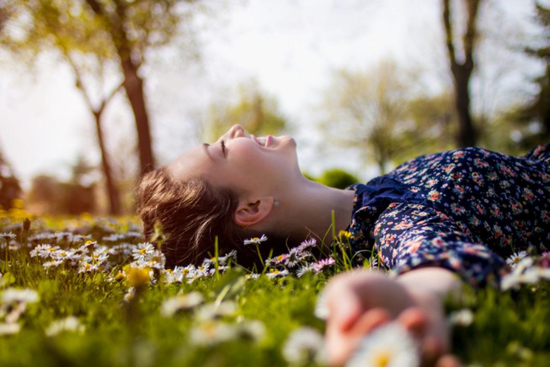 Happy woman lying on grass