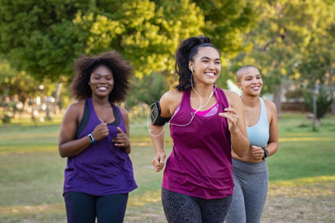 Group of female friends jogging together at park.