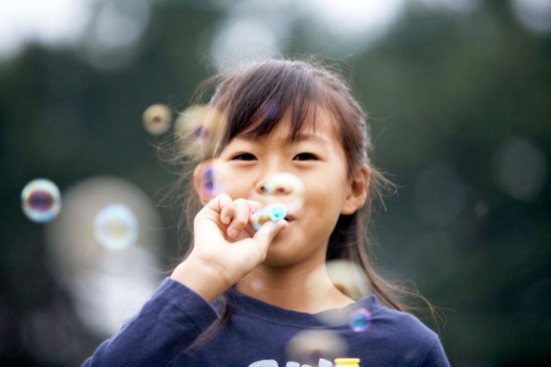 Young japanese girl blowing bubbles