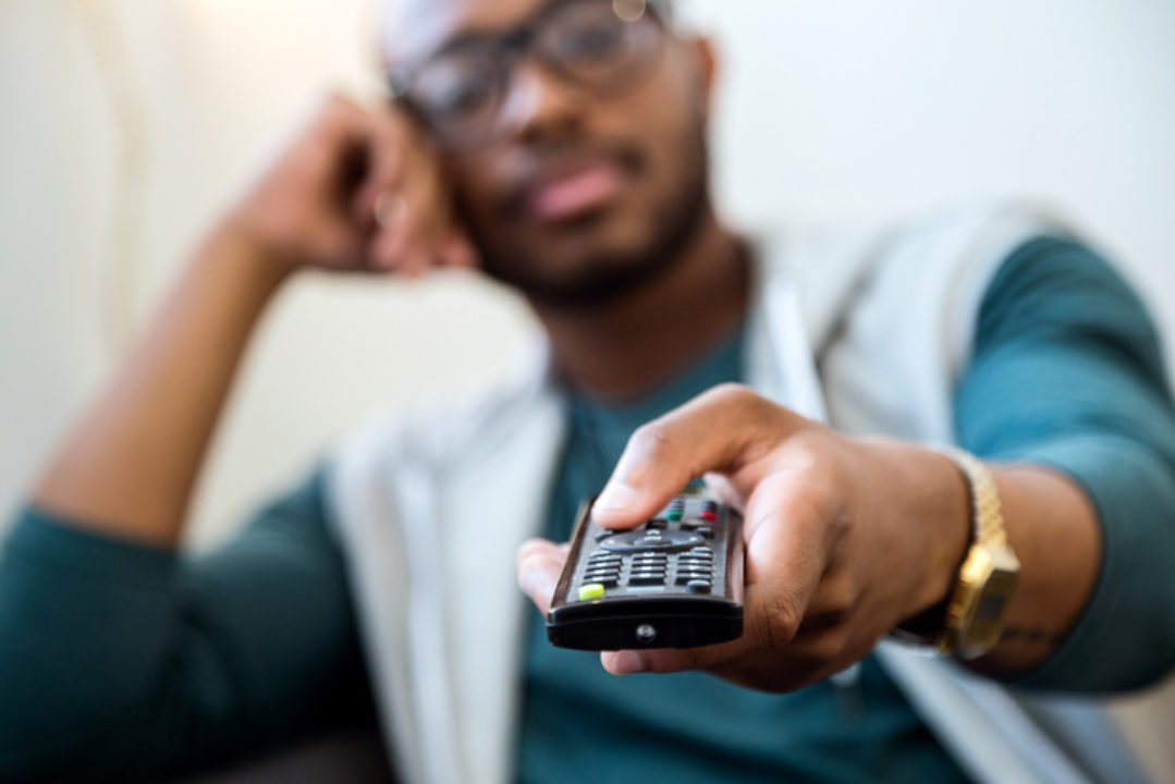 A man holds a remote control.