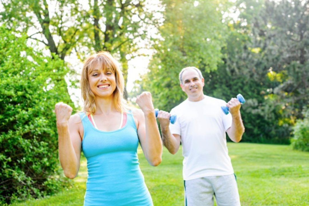 Two older people exercising outdoors