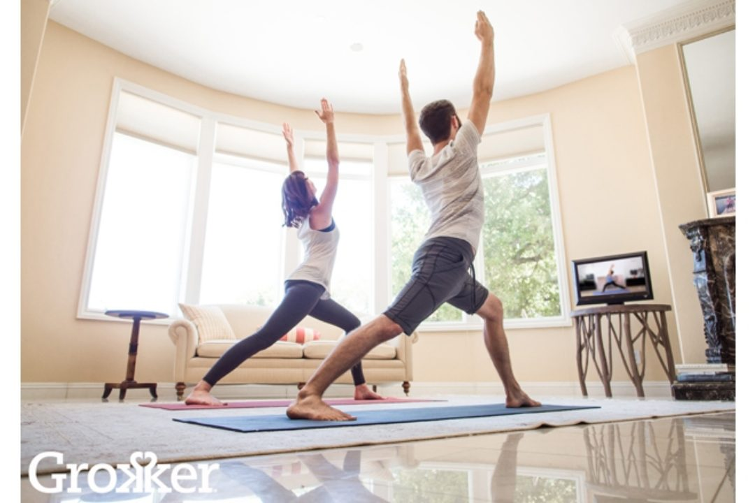 Man and woman practicing yoga at home
