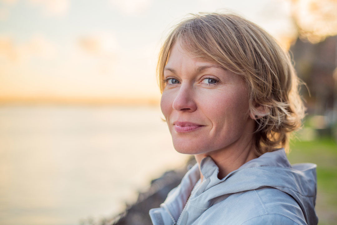 Woman smiling contently at sunset