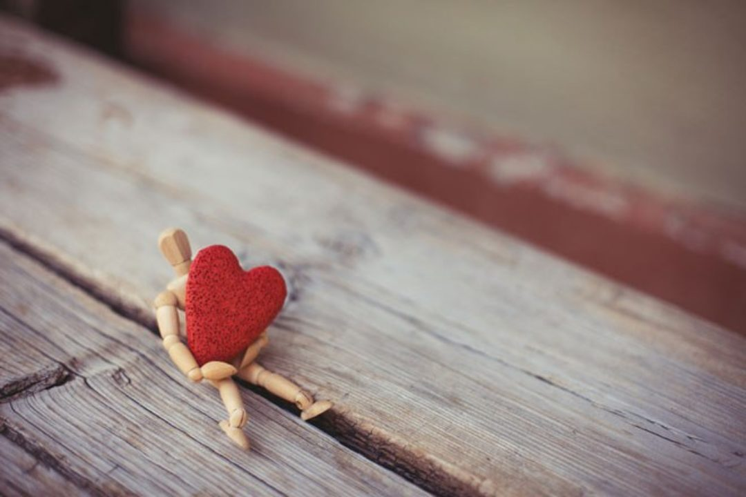 Wood figure holding red heart