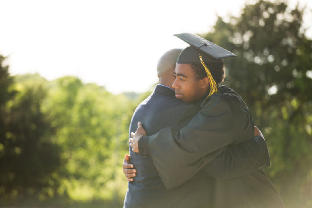 father hugging graduate