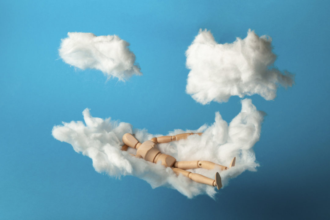 Toy man relaxing on cloud bed, meditating and feeling peace with his breathwork.