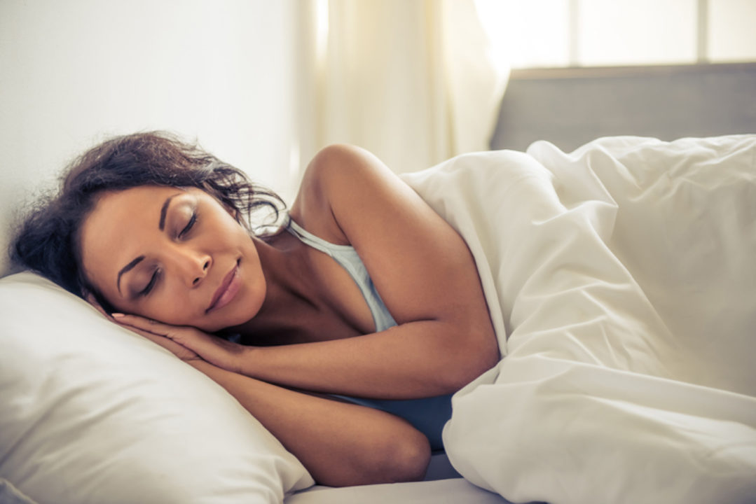 Side view of beautiful young woman smiling while sleeping in her bed at home