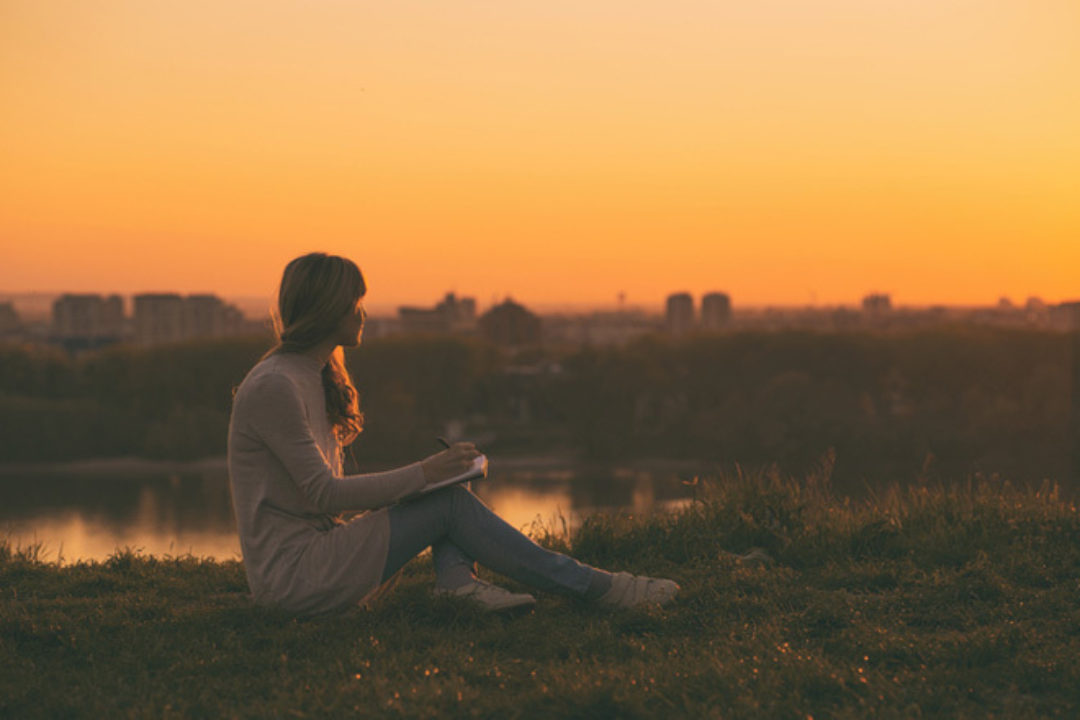 women writing at sunset