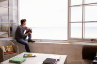 Man, isolated, looks out onto the water from his window