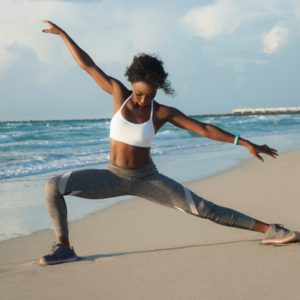 black woman doing yoga on beach