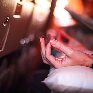 Person in airplane meditating to relax and find zen