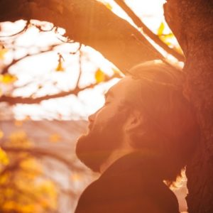 Man relaxing against tree