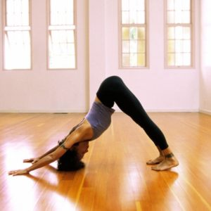 Woman in downward dog pose on wood floor