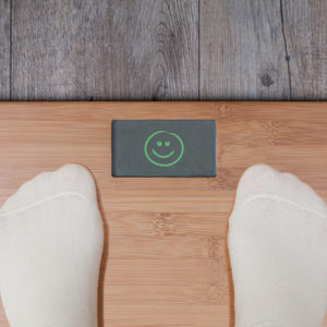 Legs of woman standing on weight scale.