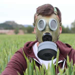 Man wearing breathing mask in wheat field.