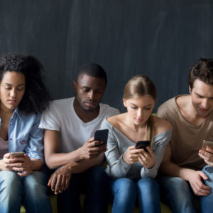 Young people sitting on couch, ignoring each other, using applications in smartphones.