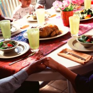 Family holding hands around dinner table