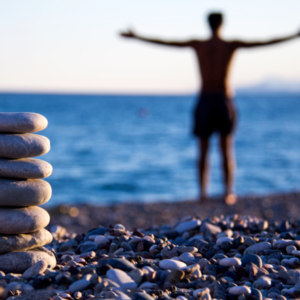 Man on beach with open arms and balancing stones