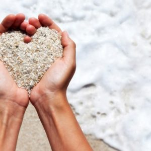 Woman holding sand in heart shape on beach