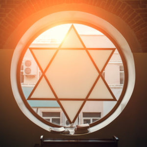 Window in synagogue in form of Star of David, six-pointed star with sunlight, Jewish symbol - stock photo