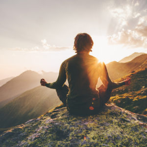 Man meditating yoga at sunset in the mountains