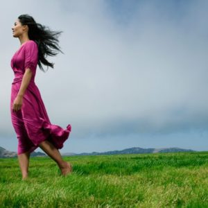 Woman barefoot in field with overcast sky