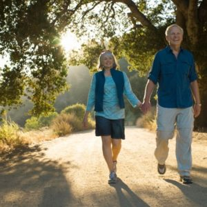 Mature couple holding hands on dirt road