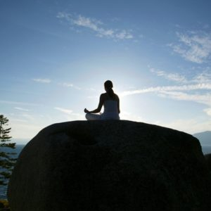 Woman meditating on large rock