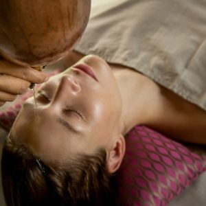 Shirodhara, an Ayurvedic healing technique. Oil dripping on the female forehead to clear third eye chakra