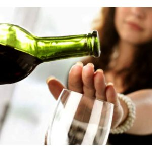 Woman placing hand over wine glass