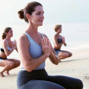 Group of people practicing yoga on beach