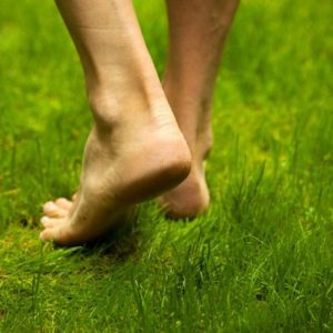 Man walking barefoot on grass