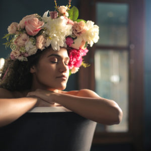 Woman wearing a flower crown soaking in the bath