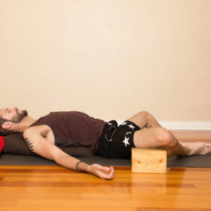 Man in supported fish yoga pose