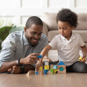 Happy dad and son building with blocks