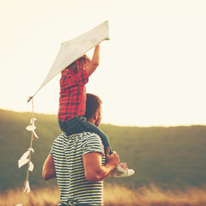 father and kid with kite