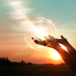 Woman's hands opened up for blessing against sunset background