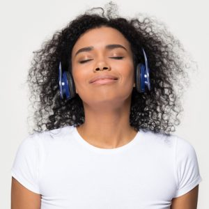Happy, calm woman wearing headphones listening to guided meditation